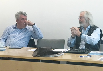 two men in blue shirts sat at a desk having a discussion