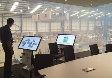 two TV screens with a factory behind them