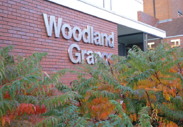 A sign saying Woodland Grange mounted on a brick wall with ferns in the foreground