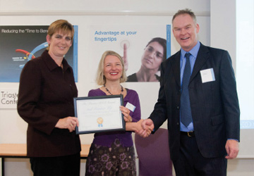 two women and a men in business dress shaking hands - the woman in the middle is holding a certificate