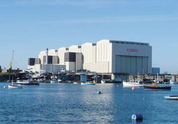 a large white building next to the sea with boats into it