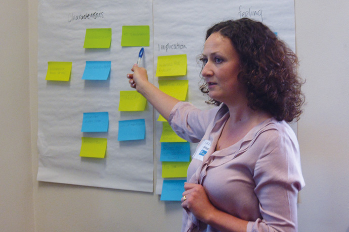 a woman pointing at a sheet of paper with post-it notes on them