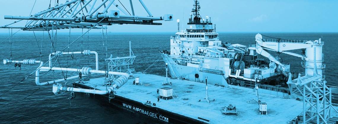 A ship at sea docking next to a platform with cranes attached with a blue filter