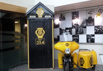 a black door with the AA written on it in yellow writing, next to a yellow motorbike and sidecar